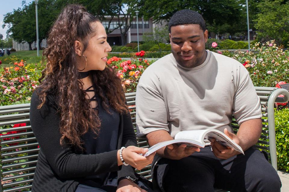 Two students looking at book on campus